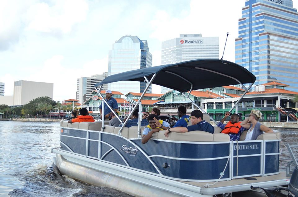 Some mentors and the mentees going together on a boat ride in downtown Jacksonville. One of the students waving behind the boat to the camera.