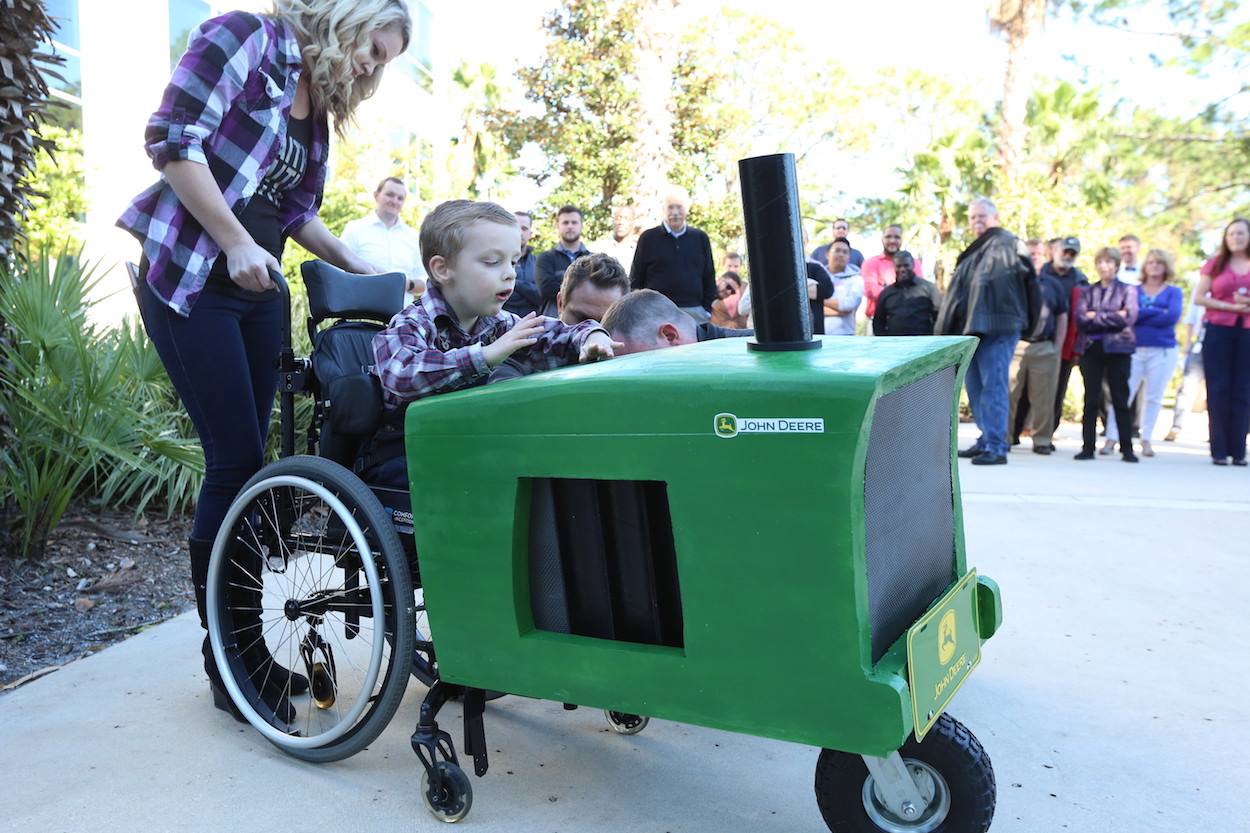 Young boy in wheelchair sits in custom tractor costume.