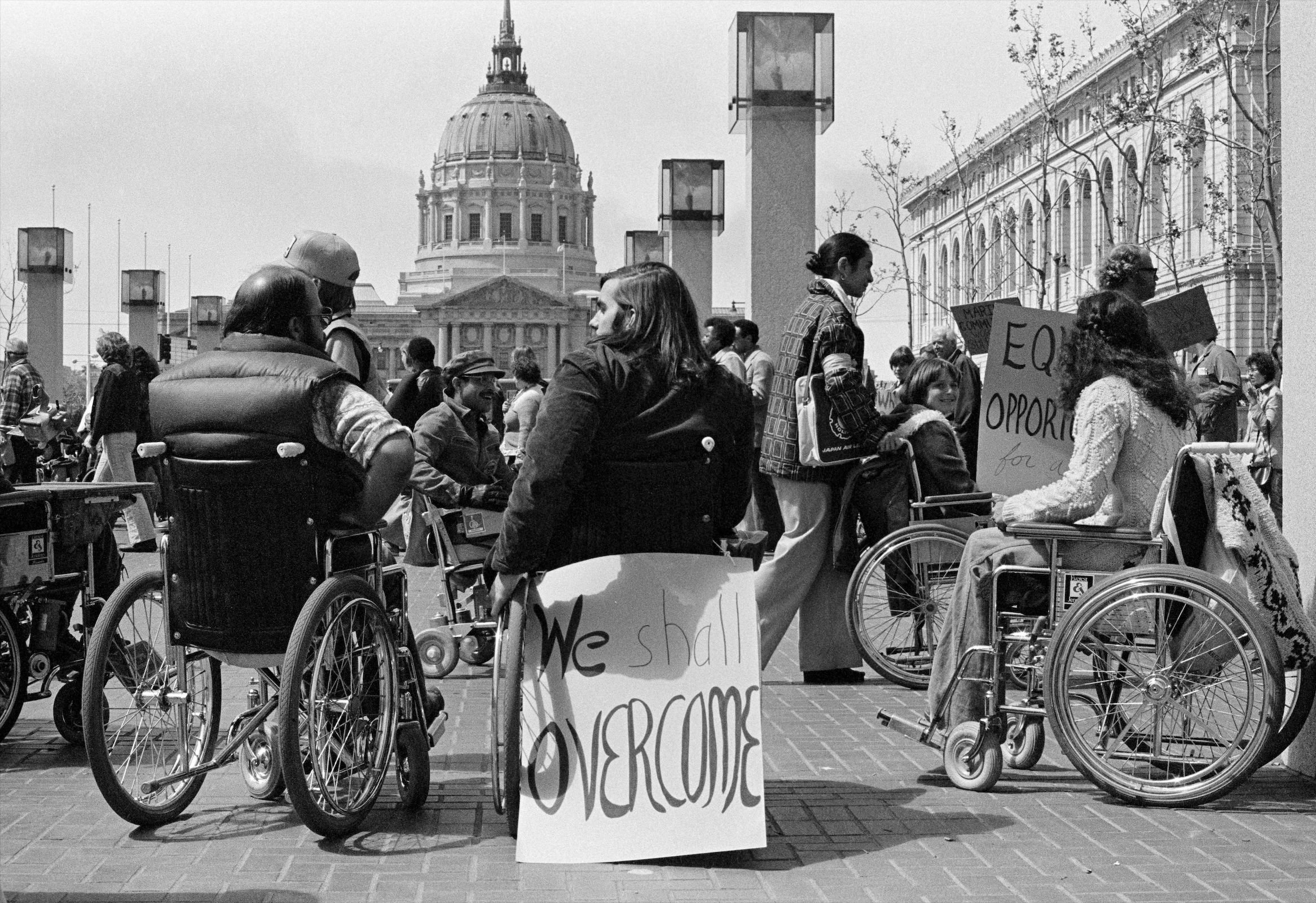 "An old photo of people using wheelchairs who are advocating for their rights. A sign is attached to the back of a wheelchair that reads ""We Shall Overcome""."