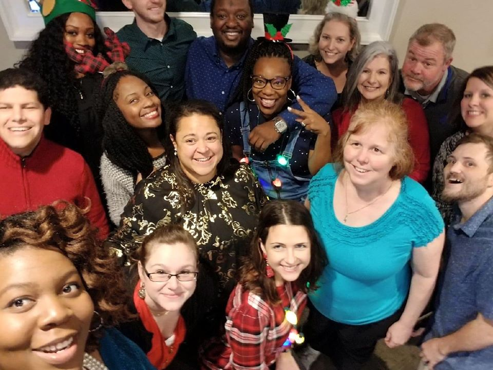 People in the staff leaning in for a group selfie, wearing festive clothing and accessories.
